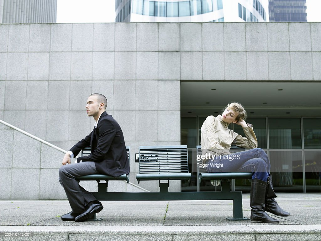 Young couple sitting either end of bench, woman looking at man : Stock Photo