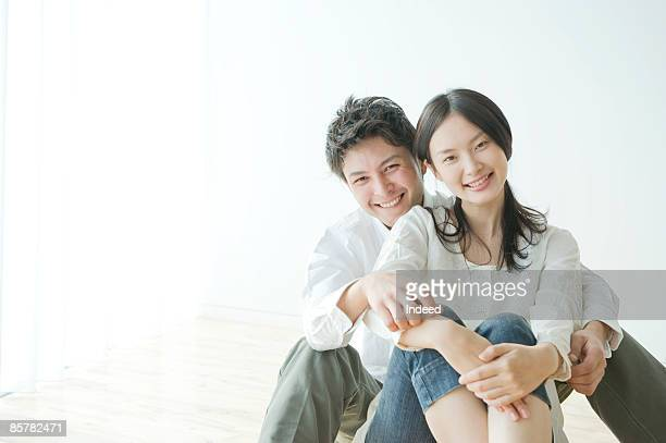 Young couple sitting floor, smiling, portrait