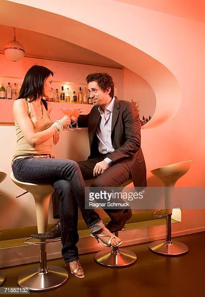 Young couple sitting in a bar drinking cocktails