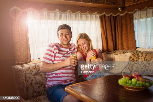 Young couple sitting in a camper van : Stock Photo