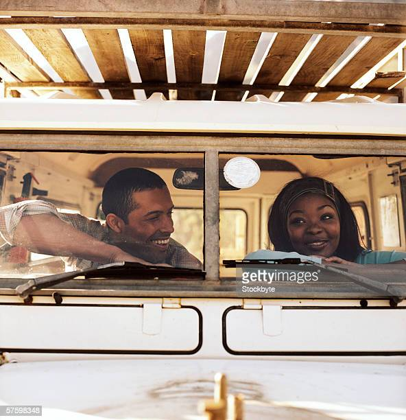Young couple sitting in a jeep and looking out the window
