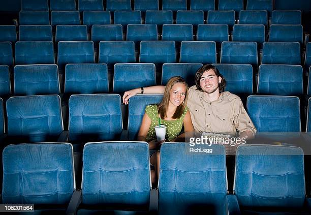 Young Couple Sitting in an Empty Movie Theater