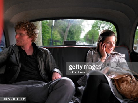 Young couple sitting in back of taxi, woman using mobile phone