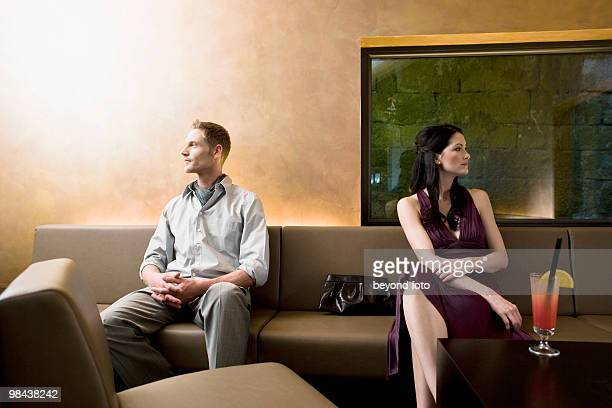 young couple sitting in bar looking away from each other