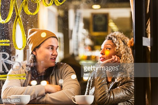 Young couple sitting in coffee shop talking : Stockfoto