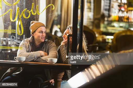 Young couple sitting in coffee shop talking : Stock Photo