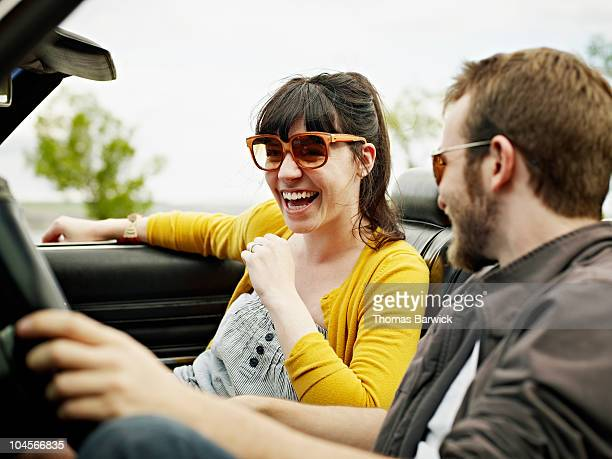 Young couple sitting in convertible woman laughing