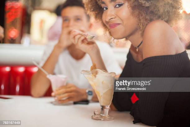 Young couple sitting in diner, eating dessert, smiling