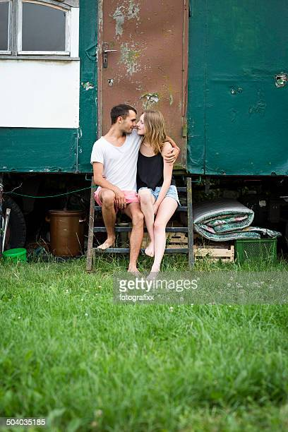 young couple sitting in front of a trailer