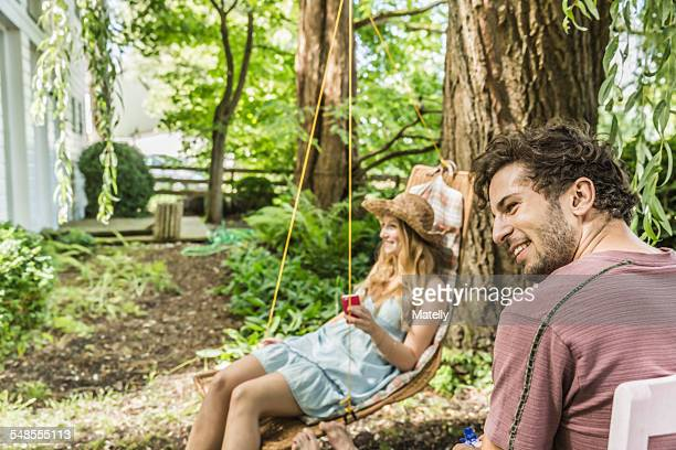 Young couple sitting in garden looking away