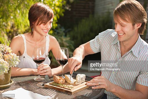 Young couple sitting in garden sharing food.