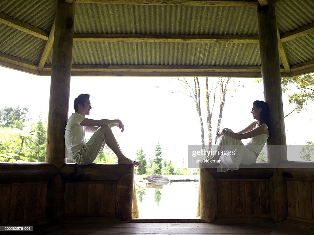 Young couple sitting in gazebo smiling at each other, side view : Stock Photo