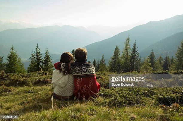 'Young couple sitting in meadow in mountains, rear view'