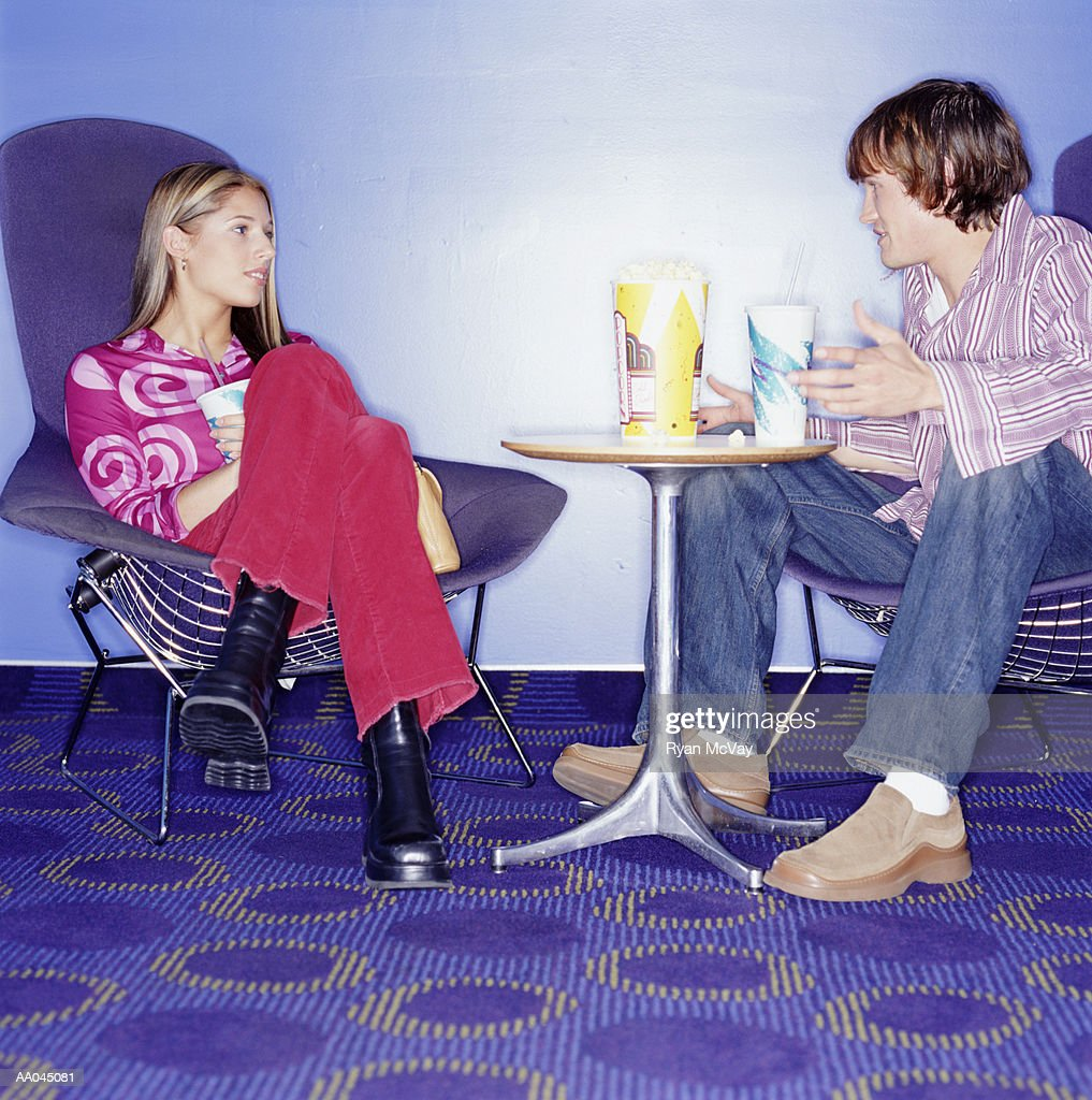 Young couple sitting in movie theater lobby talking, side view : Stock Photo