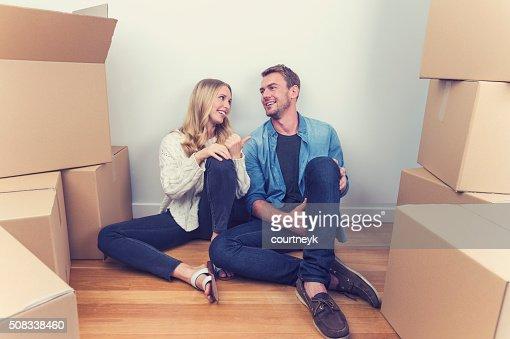 Giovane coppia seduta in una nuova casa con scatole da imballaggio.