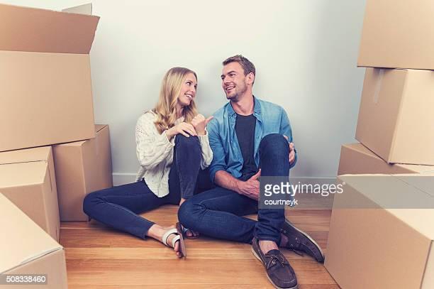Junge Paar sitzt im neuen Haus mit Umzugskartons.