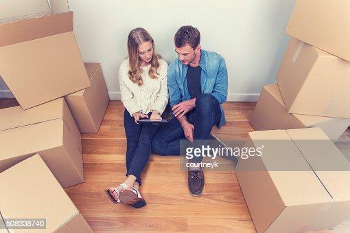 Jovem Casal sentado na nova casa com as caixas de embalagem.