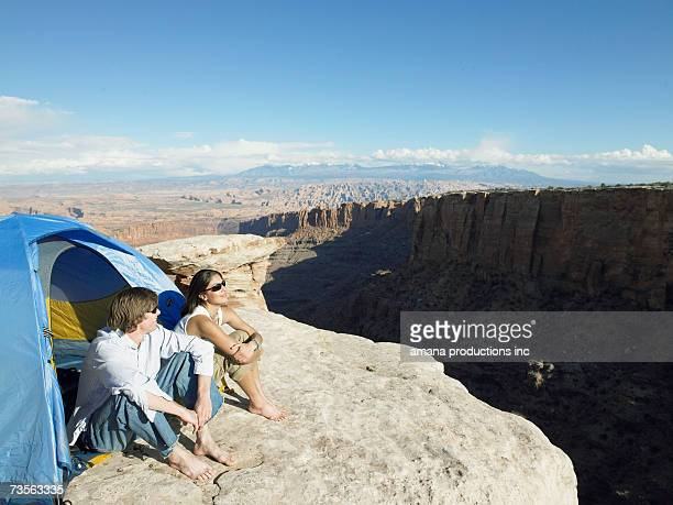 Young couple sitting in tent by cliff, high angle view, Moab, Utah, USA