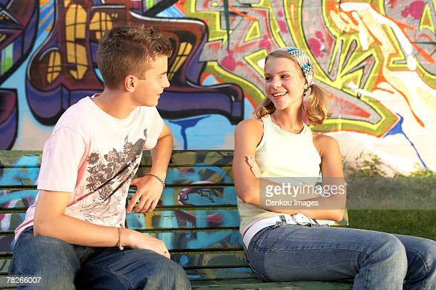 A young couple sitting on a bench.