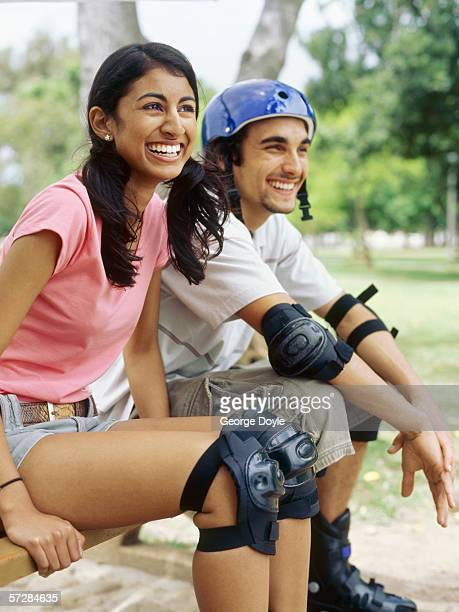 Young couple sitting on a bench wearing inline skates