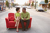 Young couple sitting on a couch outdoors