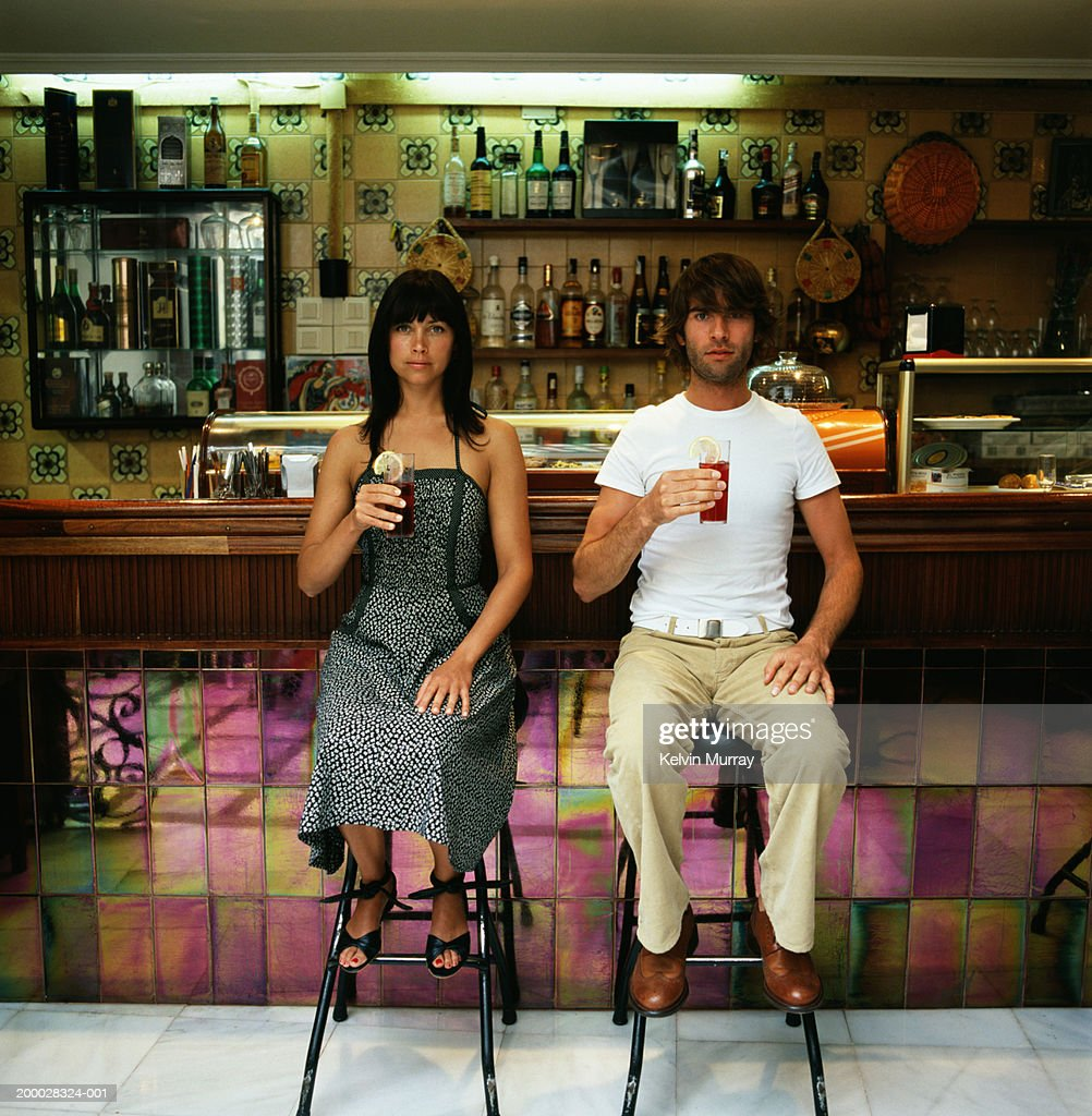 Young couple sitting on bar stools holding drinks, portrait : Stock Photo