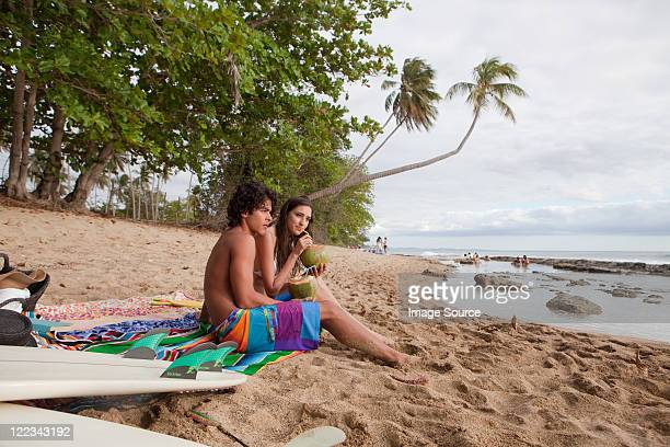 Young couple sitting on beach drinking coconut milk