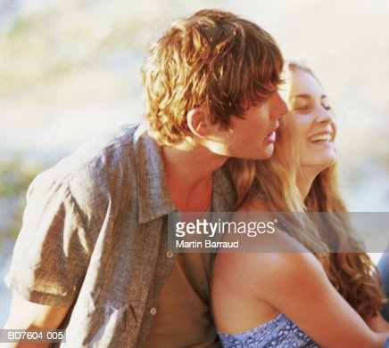 Young couple sitting on beach, early evening : Stock Photo