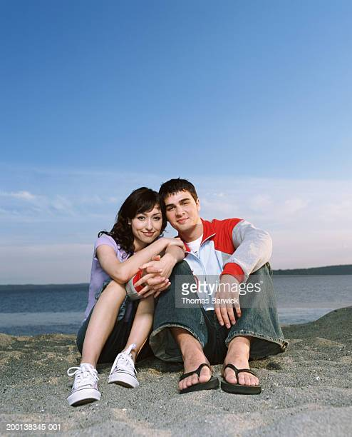 Young couple sitting on beach, holding hands, portrait