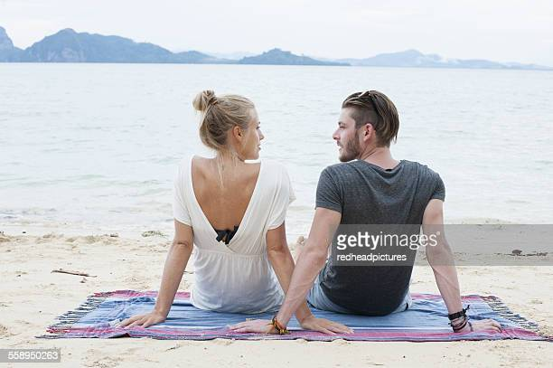 Young couple sitting on beach, Kradan, Thailand