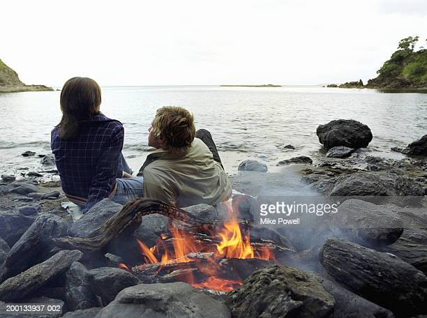 Young couple sitting on beach next to bonfire, rear view