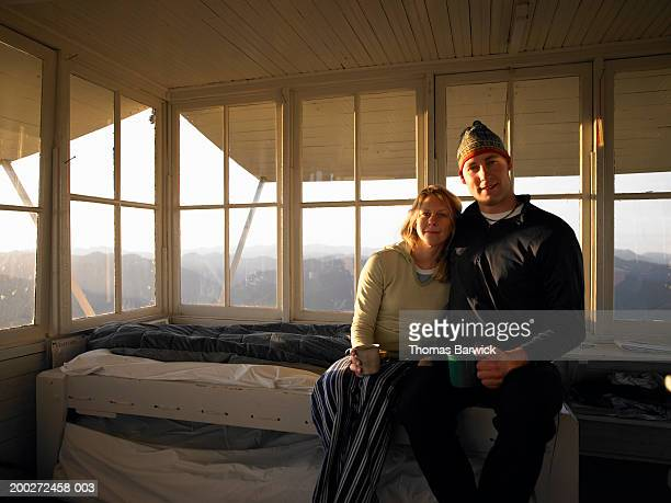 Young couple sitting on bed in mountain cabin, smiling, portrait