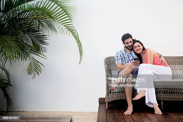 Young couple sitting on bench at home outside.