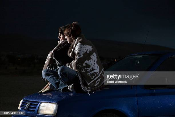 Young couple sitting on car wrapped in blanket, night