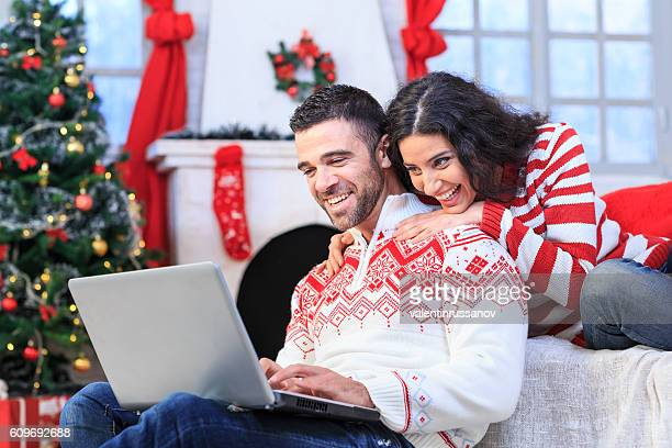 Young couple sitting on couch and using laptop at home