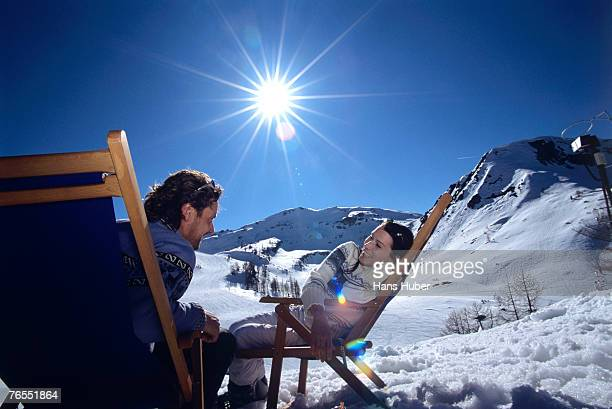 Young couple sitting on deckchairs in alps, smiling