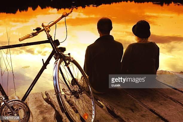 Junges Paar sitzt auf dem Dock Sonnenuntergang
