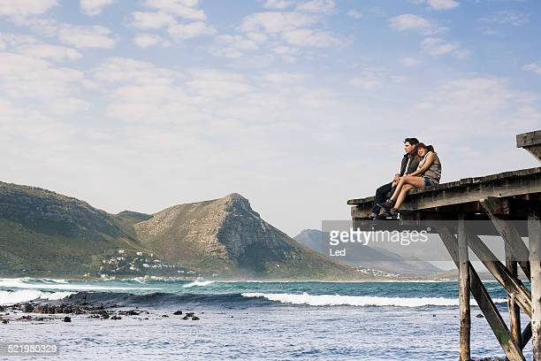 Young couple sitting on edge of old pier, Cape Town, Western Cape, South Africa