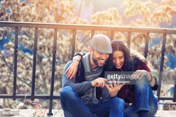 Jeune couple assis sur le sol à la recherche de photos et de téléphone