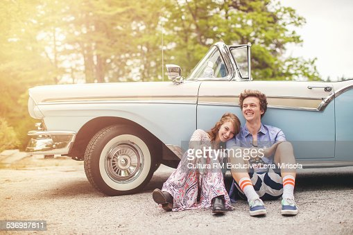 Young couple sitting on floor by convertible
