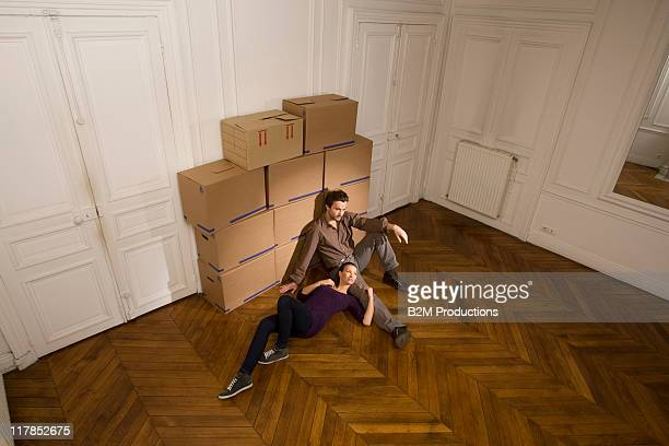 Young couple sitting on floor by packing boxes
