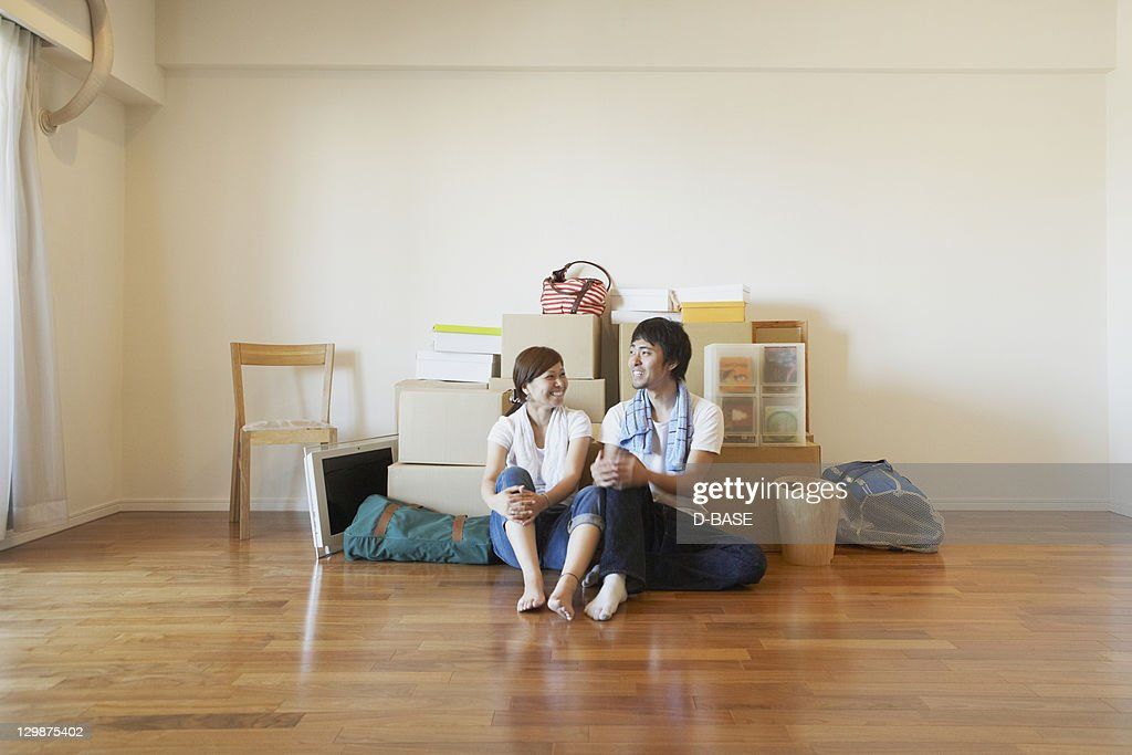 Young couple sitting on floor, smiling. : Stock Photo