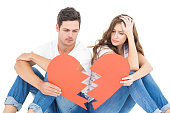 Young couple sitting on floor with broken heart on white background