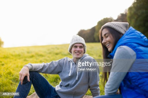 Young couple sitting on grass laughing : Stock Photo