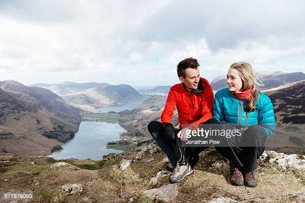 Young couple sitting on hilltop, Honister Slate Mine, Buttermere, Crummock Water, Keswick, Lake District, Cumbria, United Kingdom