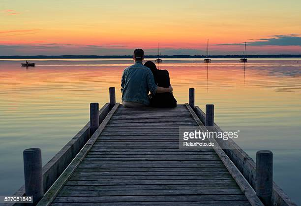 Young couple sitting on jetty at dusk