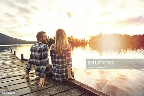 Young couple sitting on lake pier enjoying sunset