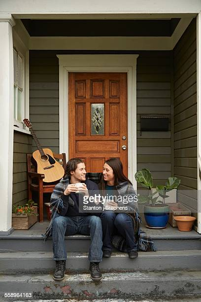 Young couple sitting on porch step chatting
