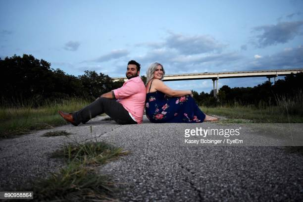 Young Couple Sitting On Road Against Sky
