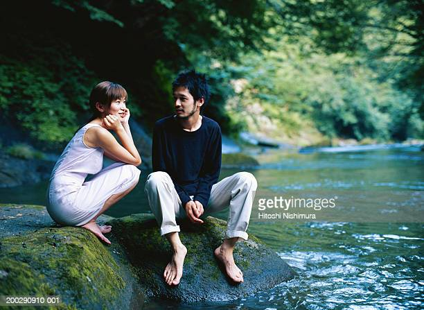 Young couple sitting on rock along river stream